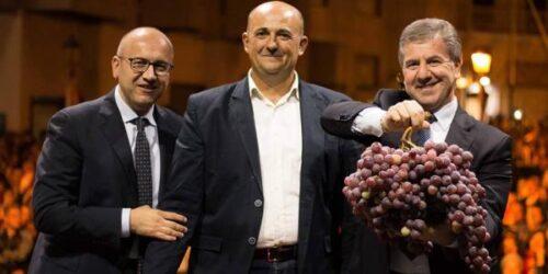 Tre uomini e un enorme grappolo d'uva