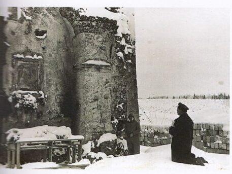 Teodoro Deamici in preghiera davanti al muro con l'affresco in ginocchio sulla neve