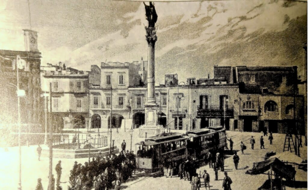 Fotografia del 1898 in bianco e nero di Piazza S. Oronzo nell'inaugurazione della linea tramvia con vettura e folla di gente