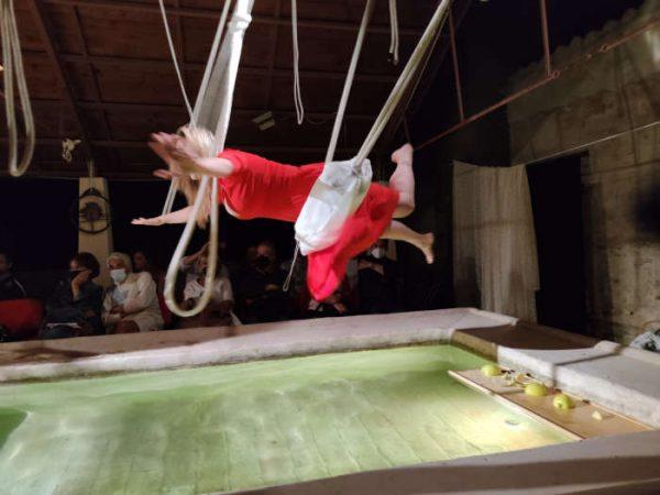 Donna con abito rosso con braccia aperte distesa su altalena sopra una vasca piena d'acqua