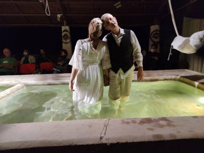 donna di spalle e uomo di fronte affiancati in piedi dentro una vasca piena d'acqua